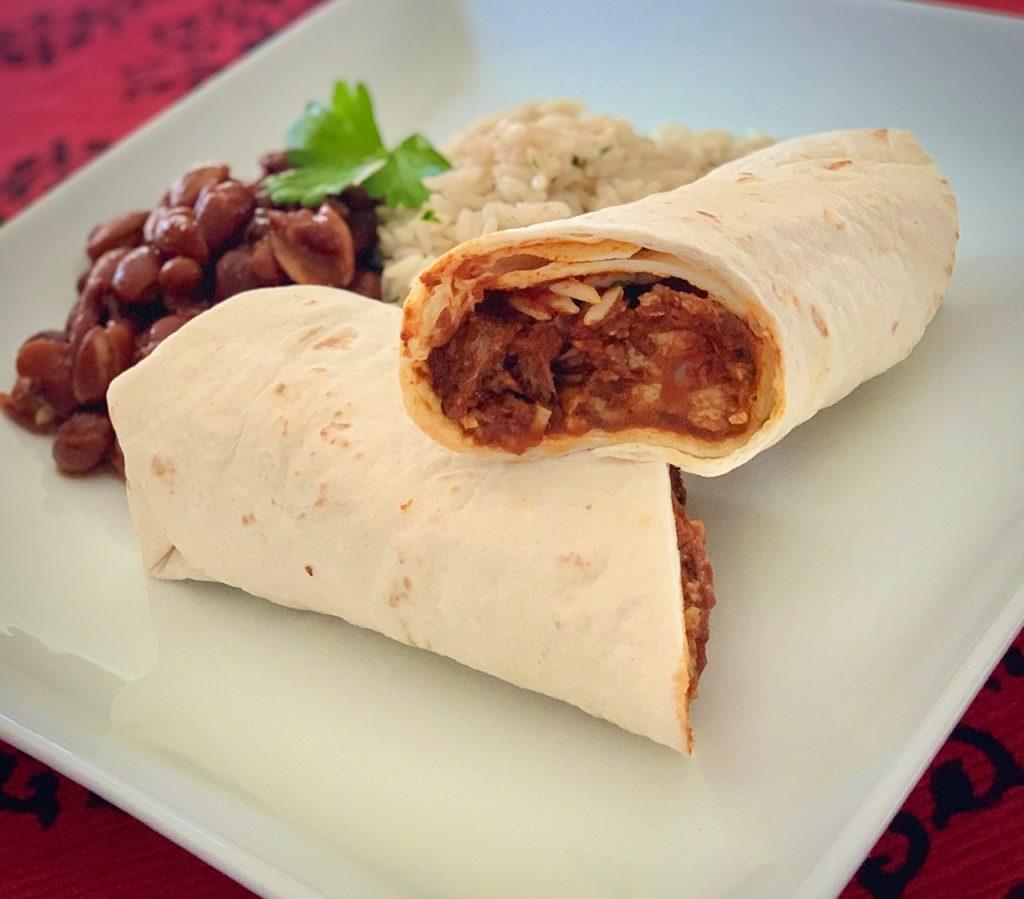 Chile Colorado burrito cut in half on a white plate