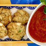 Perfect Baked Crab Cake Bites with Spicy Cocktail Sauce on a plate