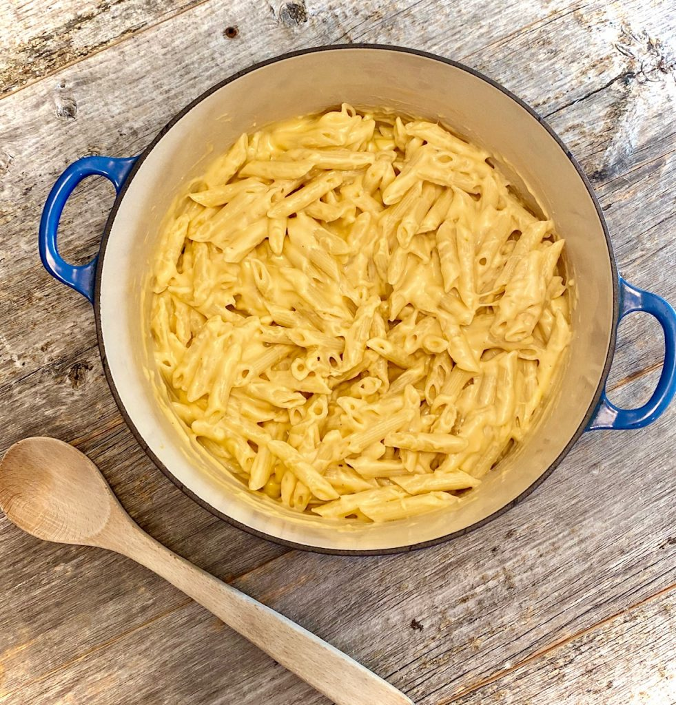 Mac and cheese on a blue pot with wooden spoon