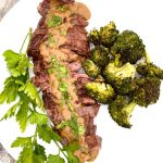 Pan seared Skirt Steak with mustard sauce and broccoli on white plate
