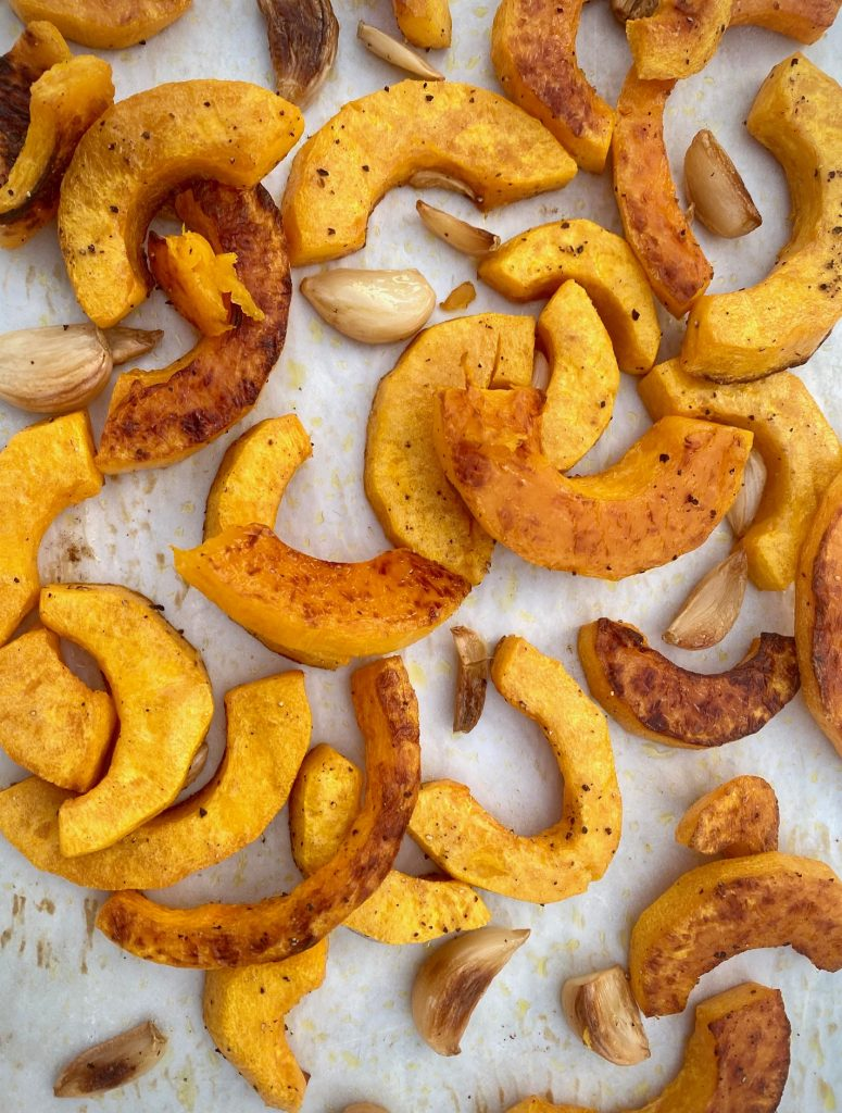 Roasted butternut squash and garlic on a baking sheet