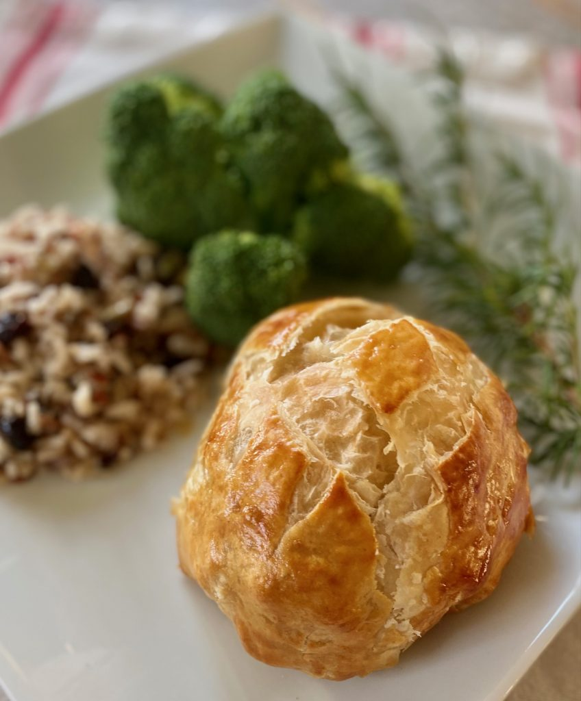 Beef Wellington with wild rice and broccoli on white plate