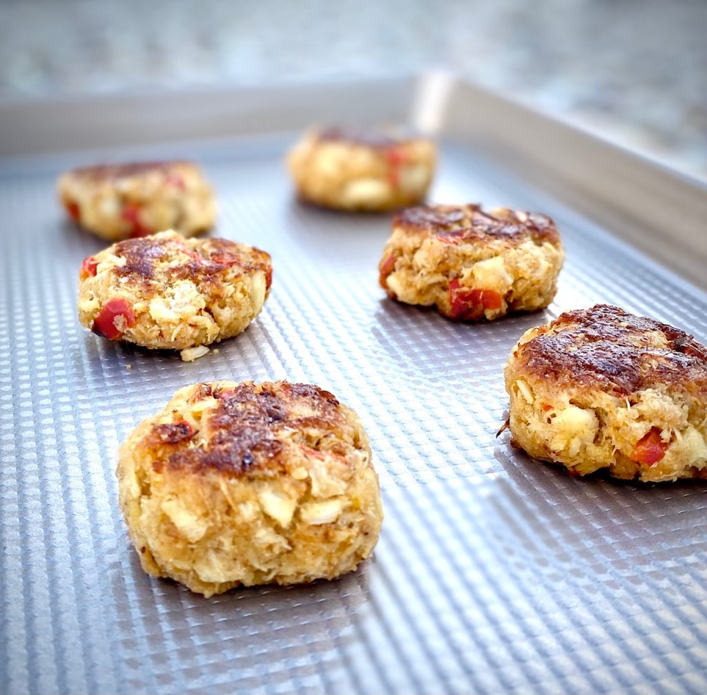 6 crab cakes on a baking sheet