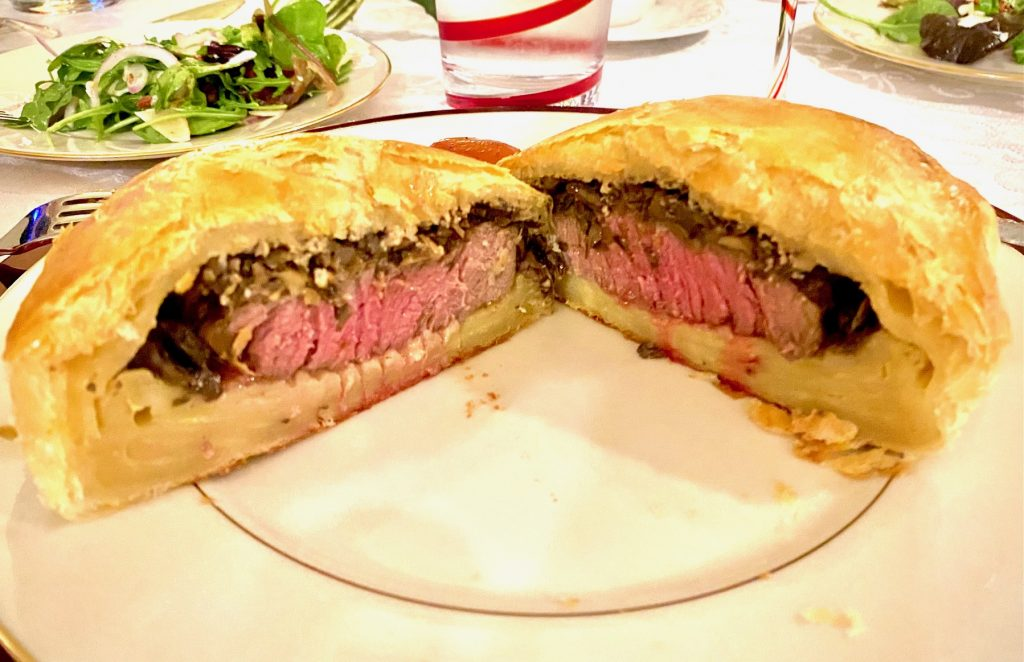 Beef wellington cut in half on a white plate