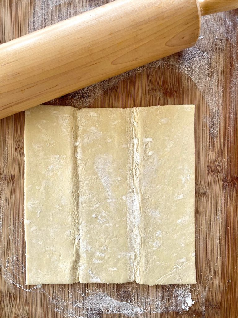 One piece of puff pastry with rolling pin