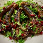 Lamb chops with pomegranate glaze on a white plate