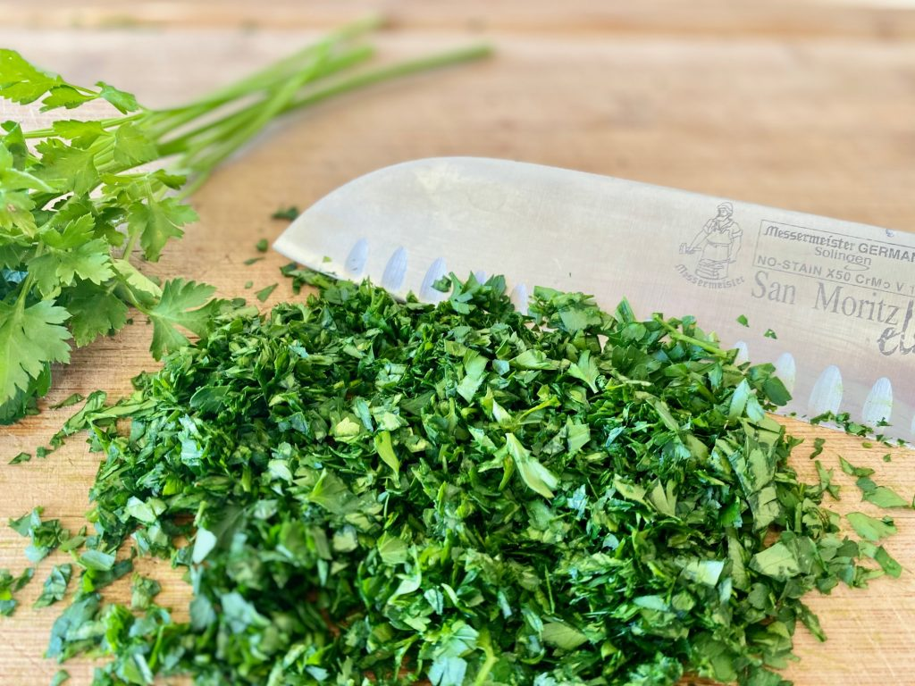 Chopped parsley and cilantro on a cutting board with a knife