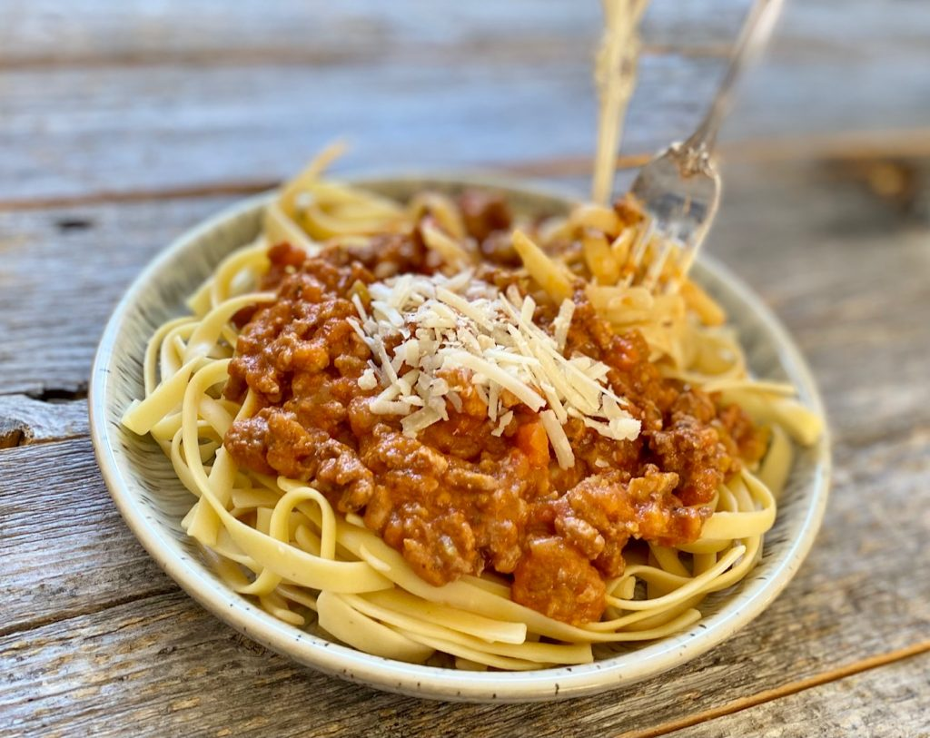 a bowl of Bolognese with pasta and parmesan