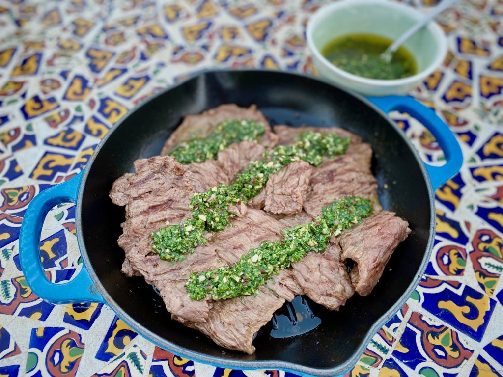 steak with chimichurri sauce in a blue grill pan