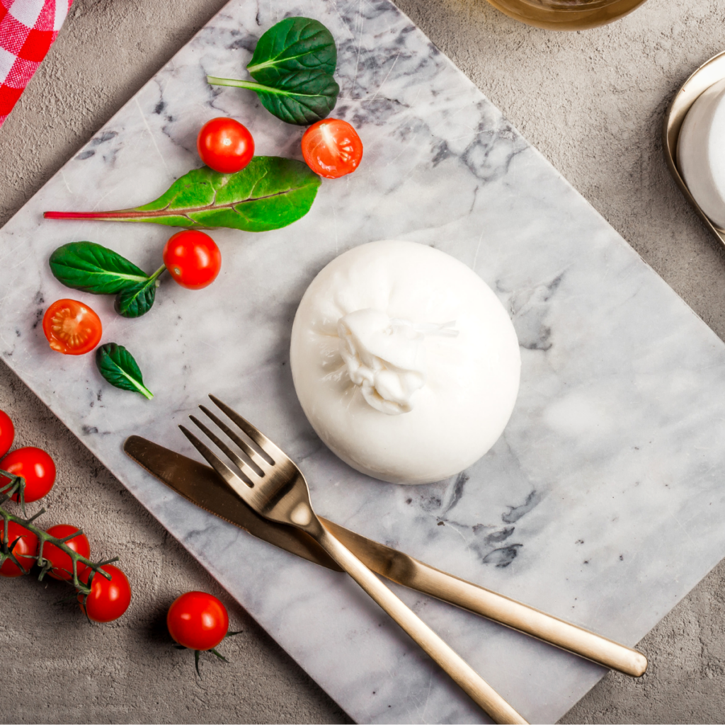 a ball of burrata with tomatoes on a piece of marble