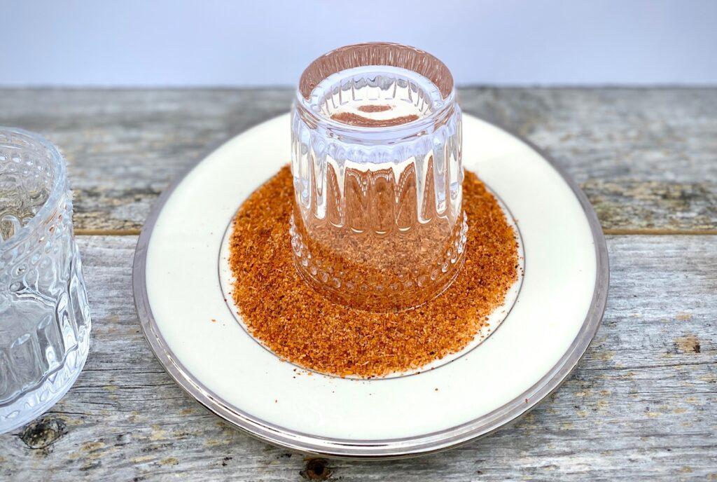 upside down glass in a plate of Tajin seasoning