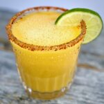 1 mango margarita with a lime and chiili on rim