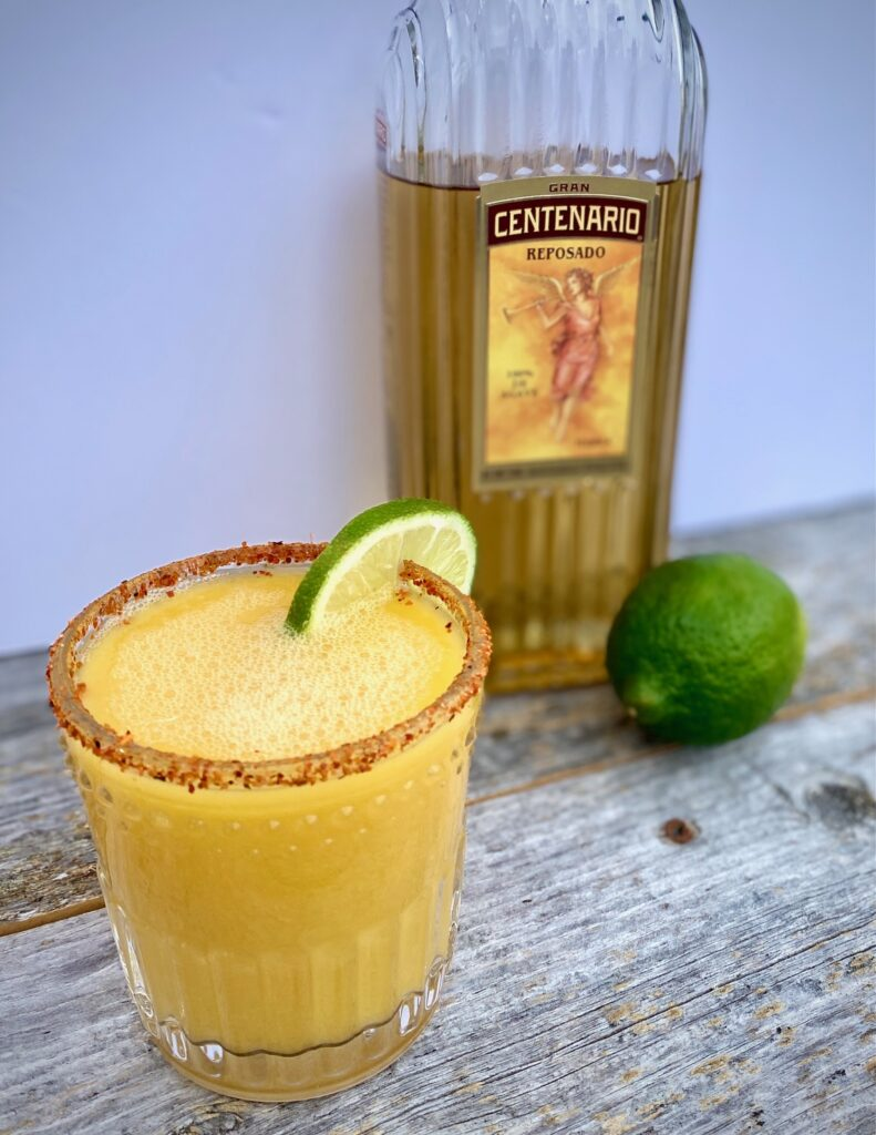 1 Spicy Mango Margarita with a lime and bottle of tequila