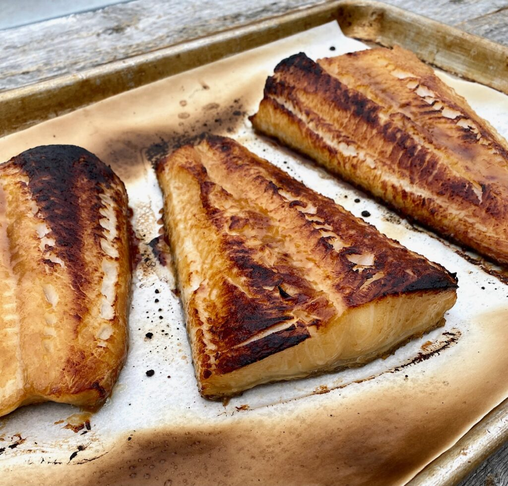 3 pieces of broiled sea bass on a baking sheet
