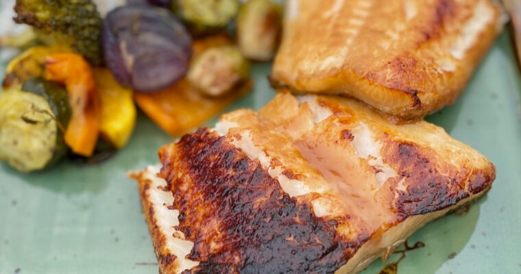 miso glazed sea bass on green plate with vegetables