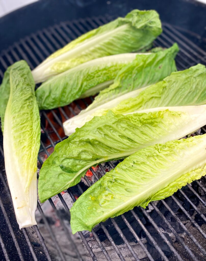 grilling lettuce heads on a charcoal grill