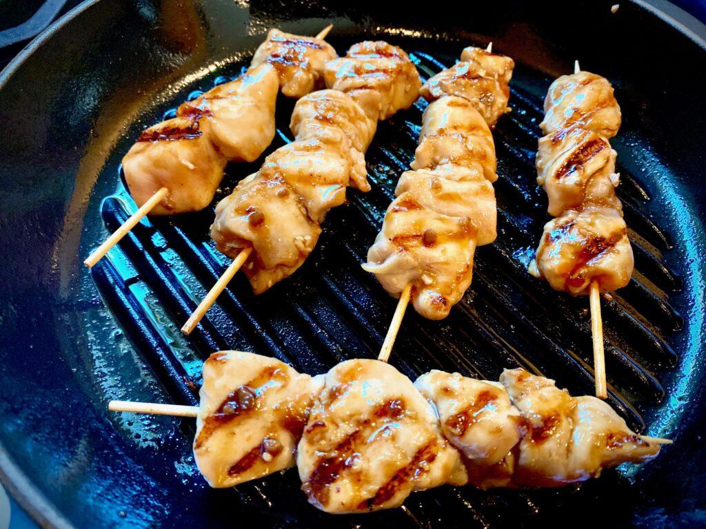 chicken skewers grilling on stove top pan